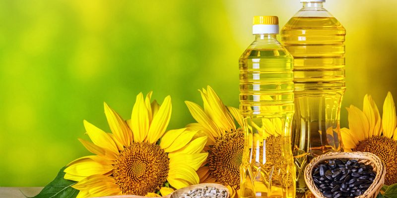 Sonnenblumenöl in Flaschen mit Sonnenblumen (Helianthus annuus), Nahaufnahme. © rustamank, Shutterstock.com.
