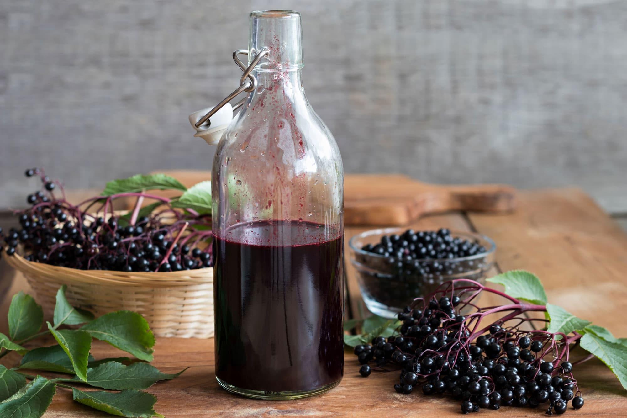 Eine Flasche selbst gemachter Holundersirup auf einem Holztisch, mit frischen Holunderbeeren im Hintergrund, © madeleinesteinbachm #92348118 123rf.com .