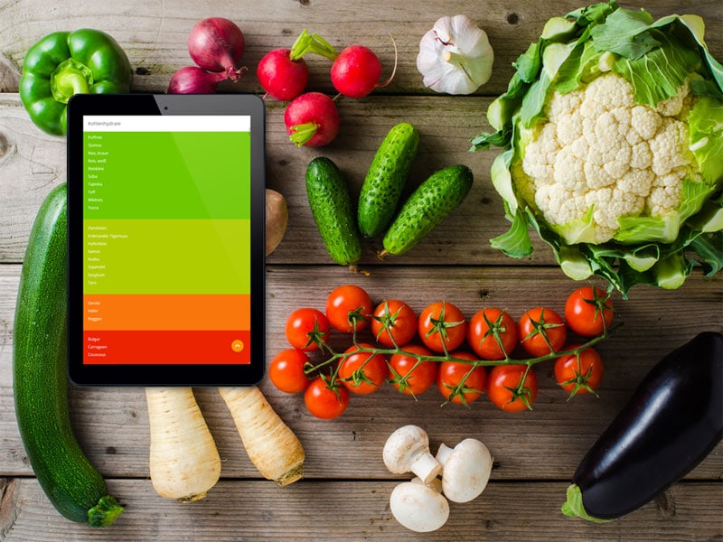 Foodfibel App und verschiedene Gemüse auf dem Tisch verteilt. Foto: Mixed vegetables on wooden table, © Leszek Czerwonka, Fotolia #104777454