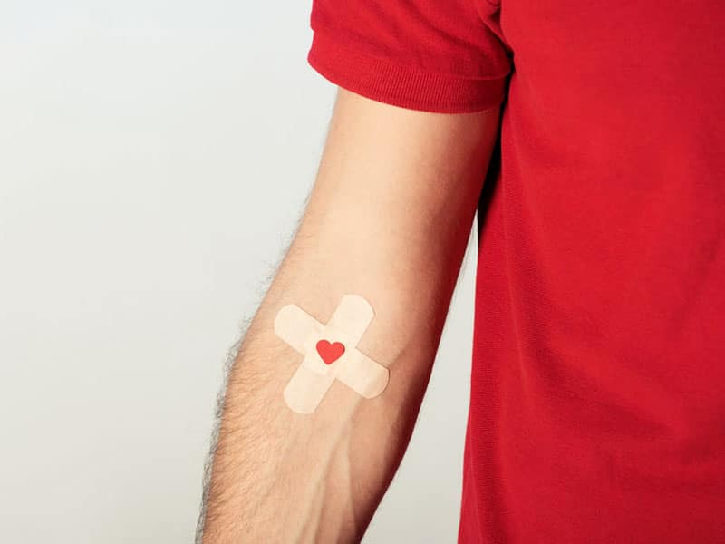 Bluttest. Partial view of patient in red t-shirt with plasters on grey background. ©  lightfieldstudios, # 118536493 123rf.com .