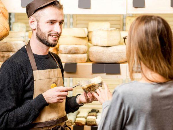 Käse kosten und probieren. Verkäufer mit einer Frau. Kundin, die einen Käse im Lebensmittelgeschäft probiert. © Olena Kachmar, # 91244461 123rf.com .