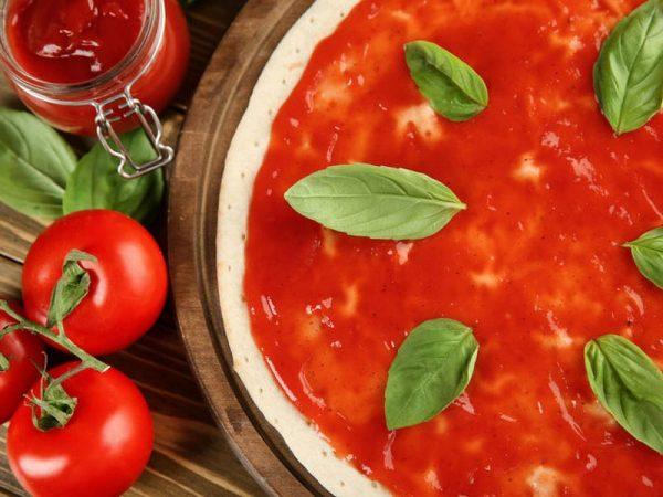 Tomaten, Ketchup im Glas, Pizza mit Tomatenmark und Basilikum-Blättern auf einem Holztisch. Foto:  © serezniy, #113164075 123rf.com