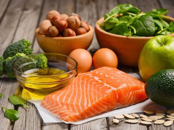 Diverse Lebensmittel auf einem Holztisch: Lachs, Olivenöl, Eier, Brokkoli, Spinat, Apfel, Avocado und Kürbiskerne. Foto: Auswahl von gesunden Produkten, © Julija Dmitrijeva, #55006043 123rf.com