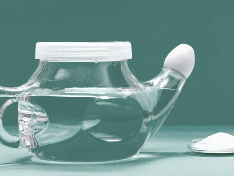 Neti Pot für Nasenspülung. Neti Pot with Soft Comfort Tip and pile of saline (sodium bicarbonate and sodium chloride) on green background. Sinus wash. Nasal irrigation. © Bohuslav Jelen, #125974995 123rf.com .