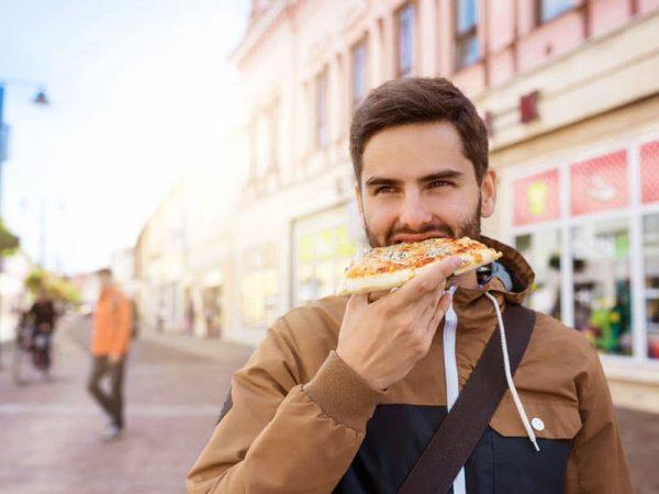 Junger Mann isst ein Stück Pizza auf der Straße. © Jozef Polc, # 46450098 123rf.com .