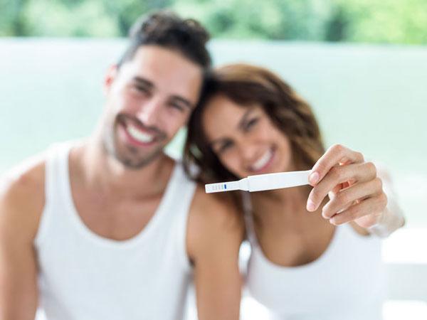 Portrait von glücklichen Paar zeigt Schwangerschaft Kit . © Wavebreak Media Ltd  123rf.com.