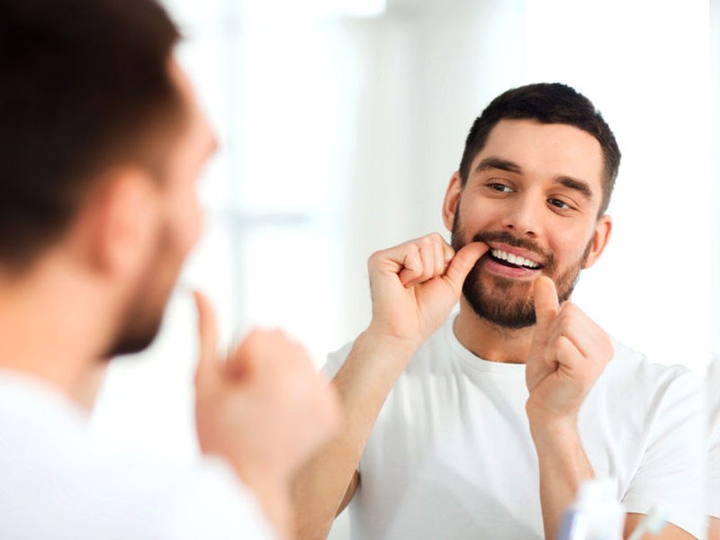 Mann bei Zahnpflege mit Zahnseide. © dolgachov  123rf.com.